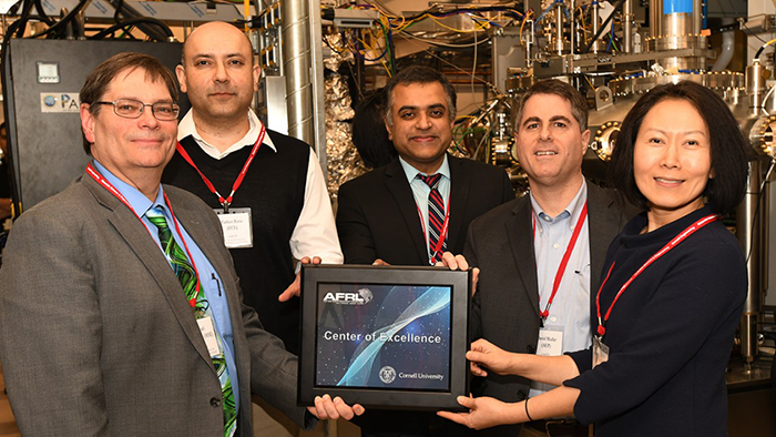Cornell researchers hold AFRL Center of Excellence plaque